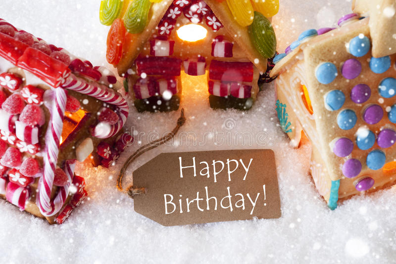 Colorful Gingerbread House, Snowflakes, Text Happy Birthday. Label With English Text Happy Birthday. Colorful Gingerbread House On Snow And Snowflakes. Christmas royalty free stock photography