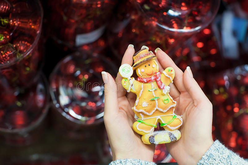 Colorful gingerbread man in female hands royalty free stock image