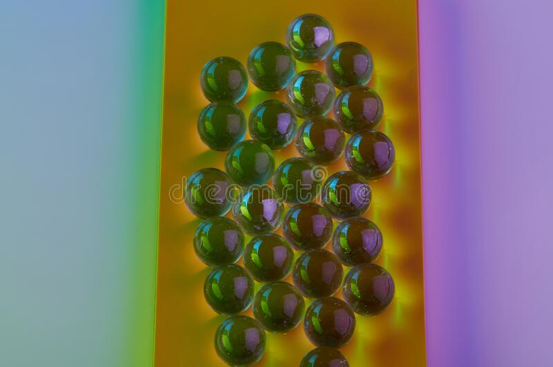Colorful glass balls. On yellow and pink background stock image