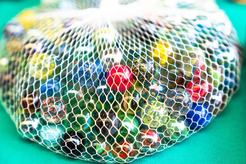 Colorful glass marbles in net stock photos