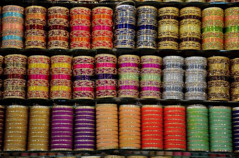 Colorful glass and metal bangles on display at shop shelf Clifton Karachi Pakistan. Karachi, Pakistan - September 8, 2016: Three rows of shelves containing stock photography
