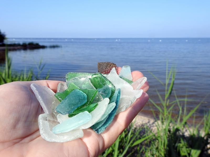 Colorful glass pieces in woman hand near Curonian spit, Lithuania. Colorful glass pieces in woman hand near Curonian spit in summer royalty free stock image