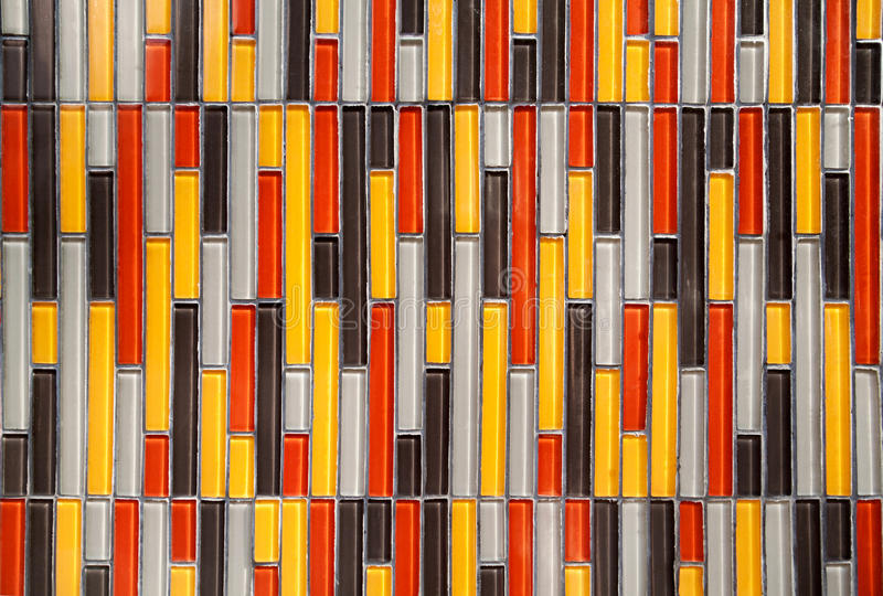 Colorful glass vertical rectangular tiled wall background. Multicolored tiles. Colorful glass vertical rectangular tiled wall background: yellow, red, white royalty free stock photography