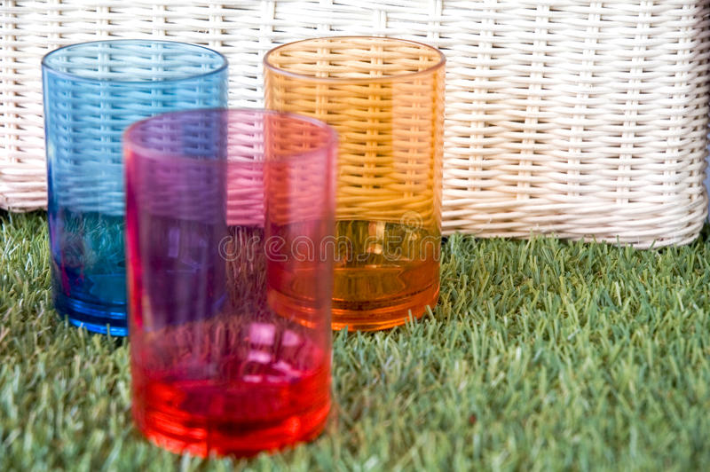 Colorful glasses with basket. Colorful glasses with white basket background stock photos