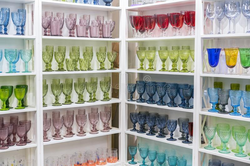 Colorful glasses and vases on the shelf in the souvenir shop. wine glasses stand on the shelves in a large supermarket.  stock photography