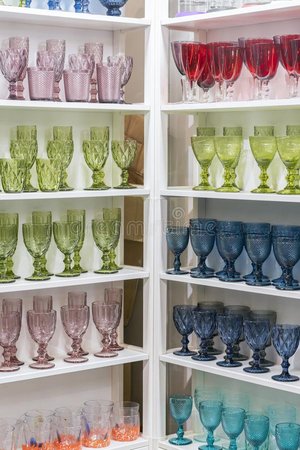 Colorful glasses and vases on the shelf in the souvenir shop. wine glasses stand on the shelves in a large supermarket. vertical. Photo stock photos