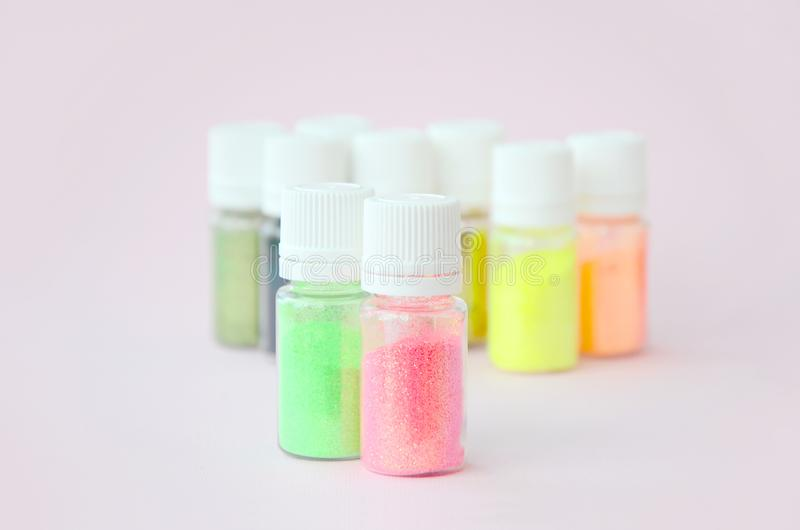 Colorful glitters lies on pastel pink background. Many round jars with multi-colored bright sparkles for nail polish stock photos