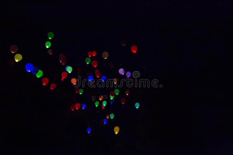 Colorful, glowing Balloons Flying in the Dark Night Sky royalty free stock image