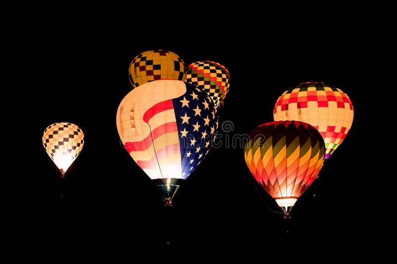 Colorful glowing hot air balloons flying at night against a black background of night sky. A group of glowing hot air balloons in the night sky at the royalty free stock images