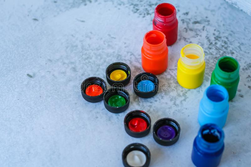 Colorful Gouache or acrylic paints in jars on white grunge background, selective focus stock images