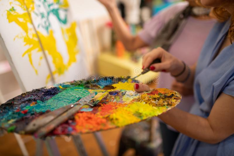Close up of young artist holding palette with gouache royalty free stock photography