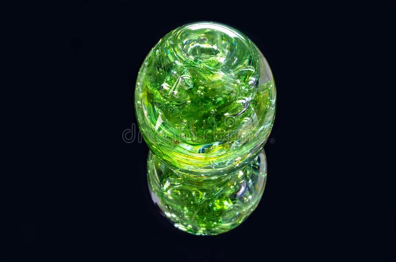 Colorful Green Sphere And Reflection. Vibrant green glass sphere and reflection isolated against black royalty free stock photo