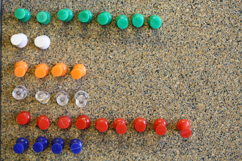 Colorful green white orange clear red blue push pins in bulletin board royalty free stock image