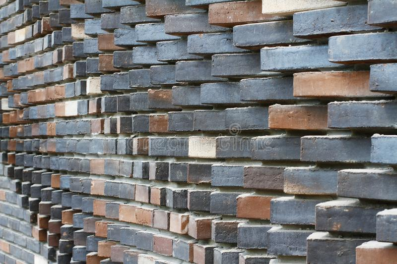 Colorful grey, beige, black, orange and brown relief brick wall. As background, texture stock image