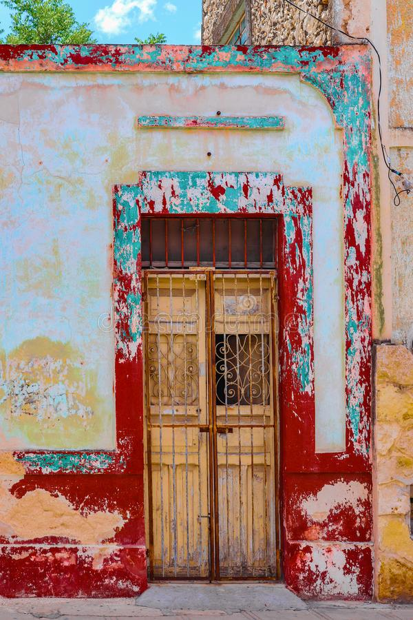 Colorful grunge around broken down door with wrought iron accents and locked bars in front on street in Merida Yucatan Mexico stock image