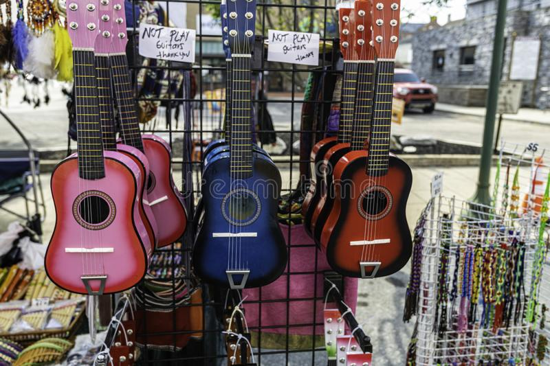 Colorful guitars hanging at street festival royalty free stock images