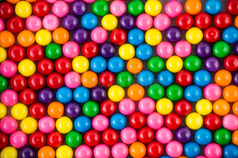 Colorful gumballs. Brightly colored gum balls laying flat, background royalty free stock images