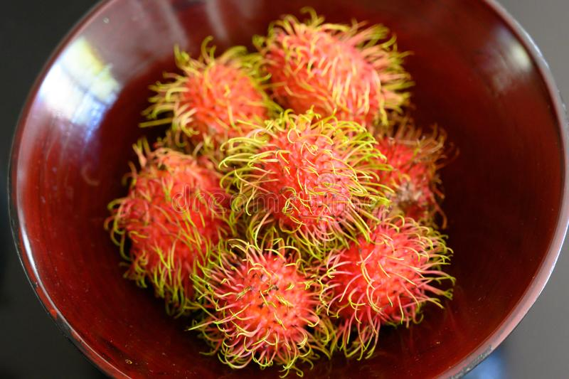 Rambutan exotic fruit of the lychee family on market in Saigon, Vietnam. Fresh lychees stapled on market in Ho-Chi-Minh-City royalty free stock image