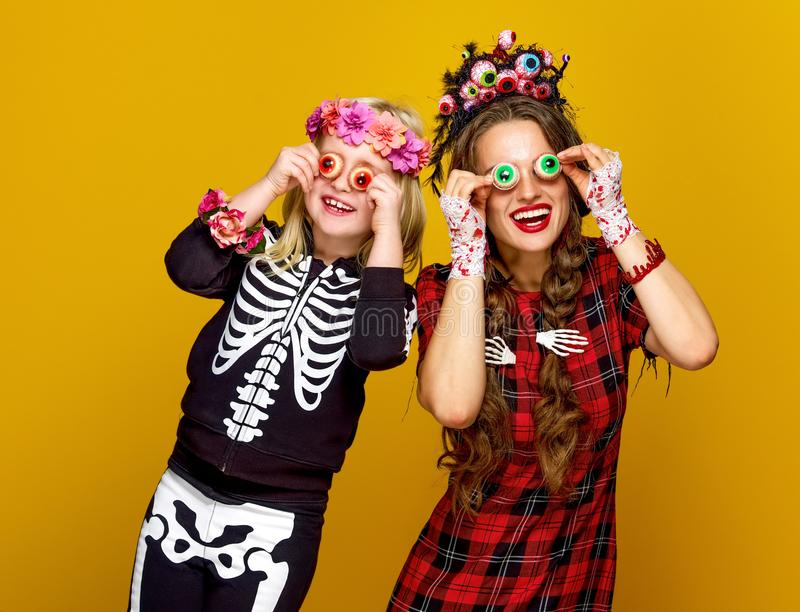 Mother and daughter in halloween costume having fun time stock photos