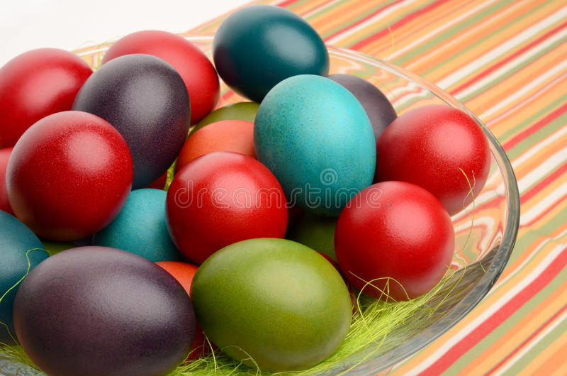 Colorful hand dyed easter eggs in a bowl on a table with striped tablecloth. royalty free stock photography