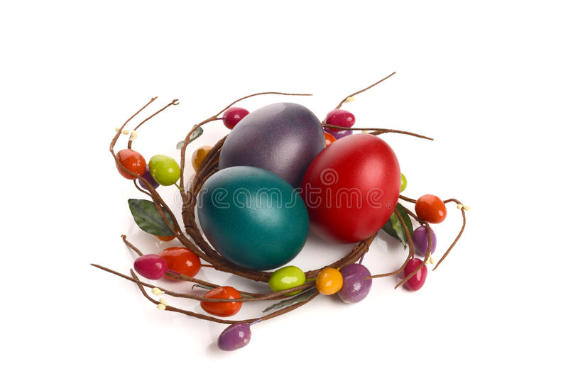Colorful hand dyed easter eggs with circle easter egg nest decoration around them. stock image