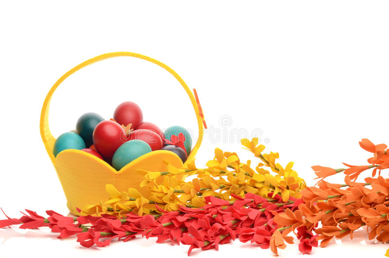 Colorful hand dyed easter eggs in a yellow basket, decorations with spring flowers royalty free stock photos