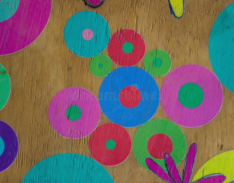 Colorful hand painted circles and flowers for background use. Colorful circles and flowers hand painted onto a wooden surface image for background use with copy royalty free stock photo