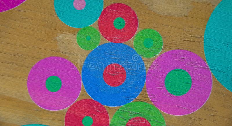 Colorful hand painted circles and flowers for background use. Colorful circles and flowers hand painted onto a wooden surface image for background use with copy royalty free stock photography