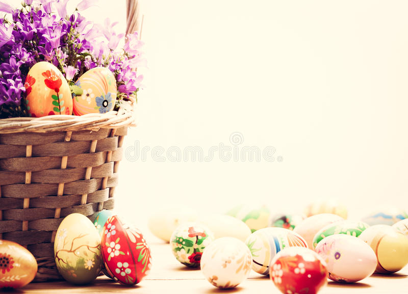 Colorful hand painted Easter eggs in basket and on wood. Handmade vintage decoration royalty free stock images
