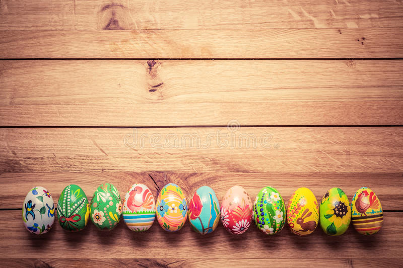 Colorful hand painted Easter eggs on wood. Unique handmade, vintage design. royalty free stock photography