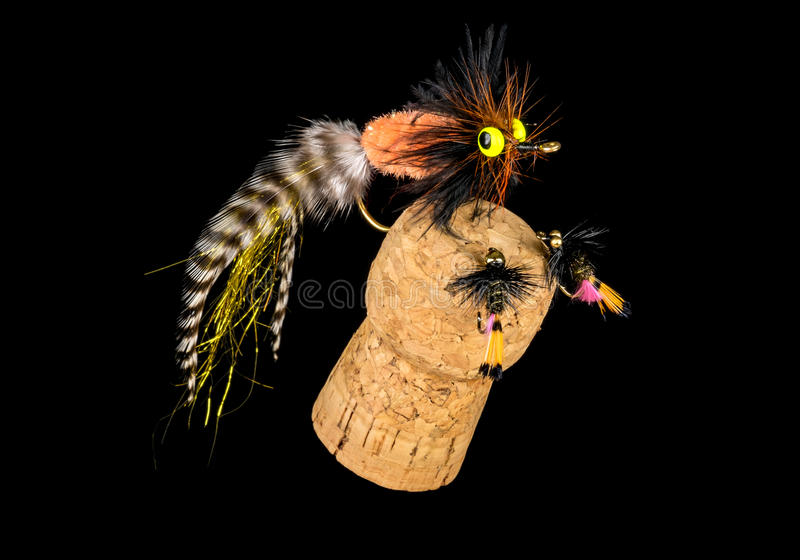Colorful Hand Tied Fishing Flies Displayed on Champagne Cork 11. Colorful Hand Tied Fishing Flies Displayed on Champagne Cork Isolated on Black 11 stock photos