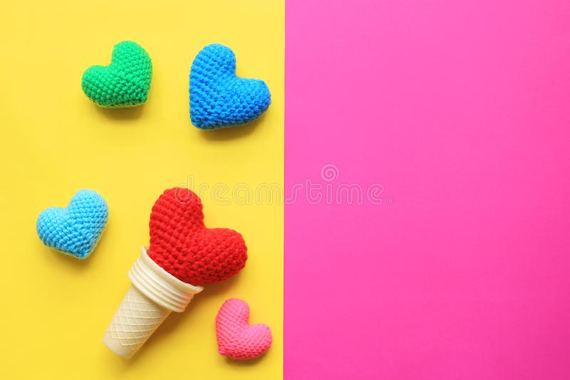 Colorful of Handmade crochet heart in waffle cup on yellow and pink background for valentines day stock image