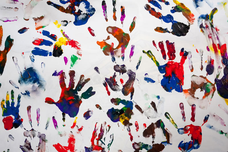 Colorful handprints hands on a white canvas. Multiple colorful children handprints on white canvas royalty free stock images