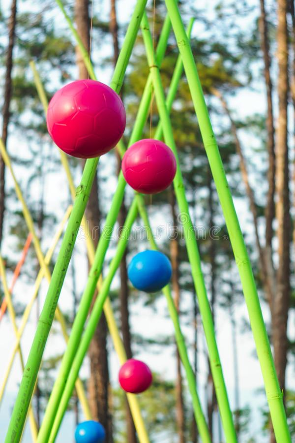 Colorful hanging balls over rope wooden ladder in adventure park in forest royalty free stock images