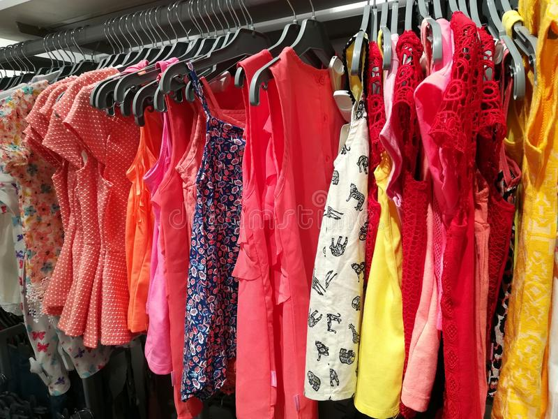 Hanging dresses. Colorful hanging clothes in a store - dresses royalty free stock photo