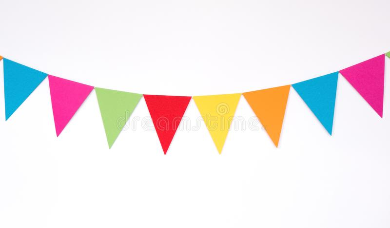 Colorful hanging paper flags on white wall background, decor items for party, festival, celebrate event stock image