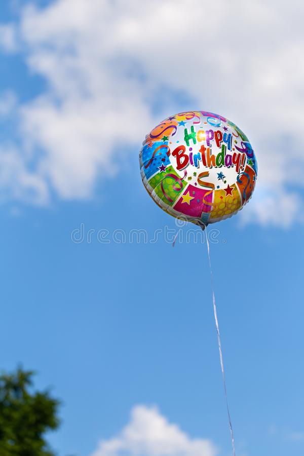 Colorful happy birthday balloon on a blue sky background royalty free stock photo