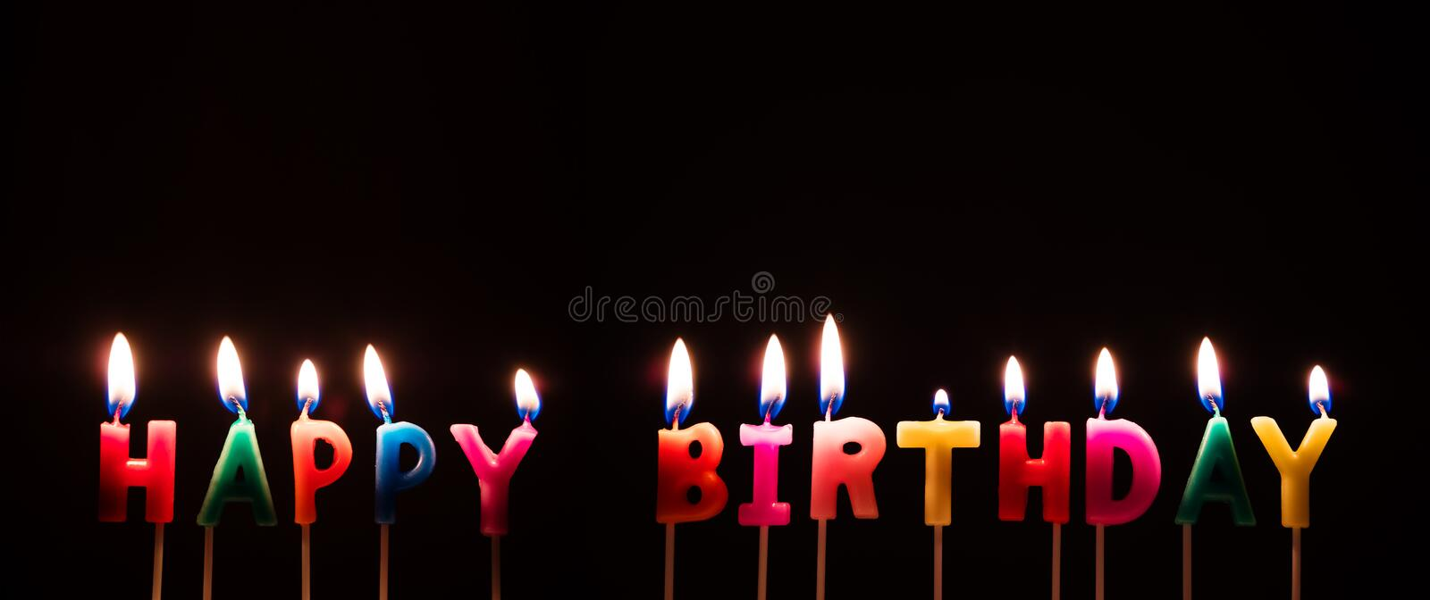 Colorful Happy Birthday Candles, on black background royalty free stock image