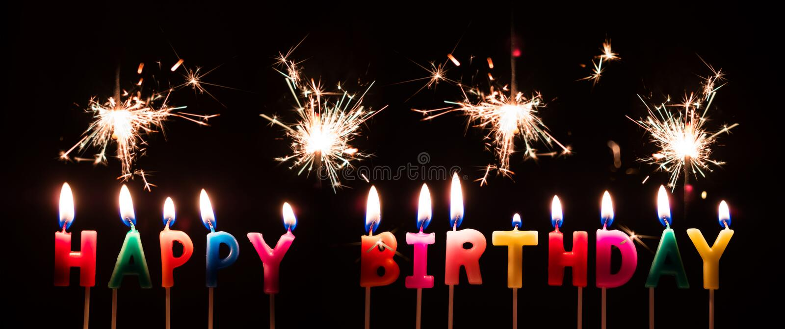Colorful Happy Birthday Candles with Sparkler Fireworks, on black background royalty free stock photography