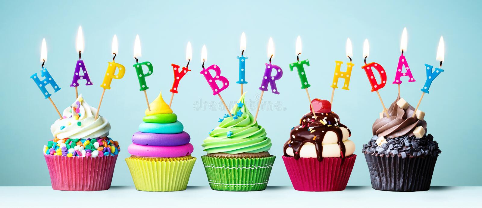 Colorful happy birthday cupcakes stock photography