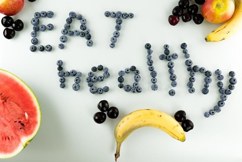 Colorful healthy fruit and berries with text. Horizontal view of colorful healthy fruit and berries with text `eat healthy` written in blueberries royalty free stock photography