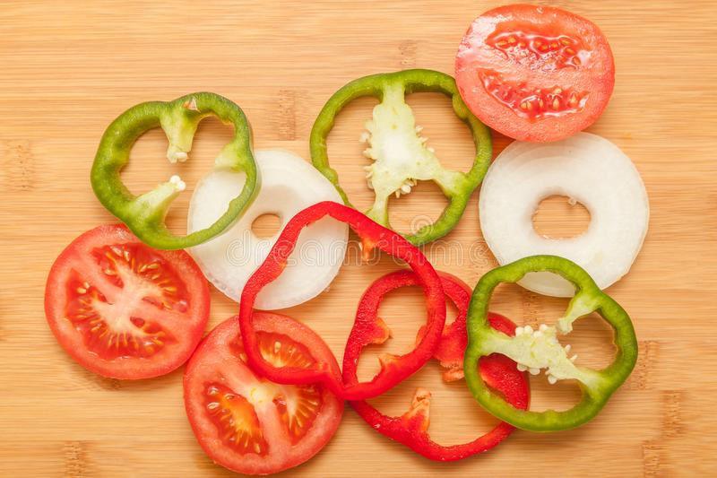 Colorful healthy vegetables - pepper, onion and tomato. On a wooden background royalty free stock photography