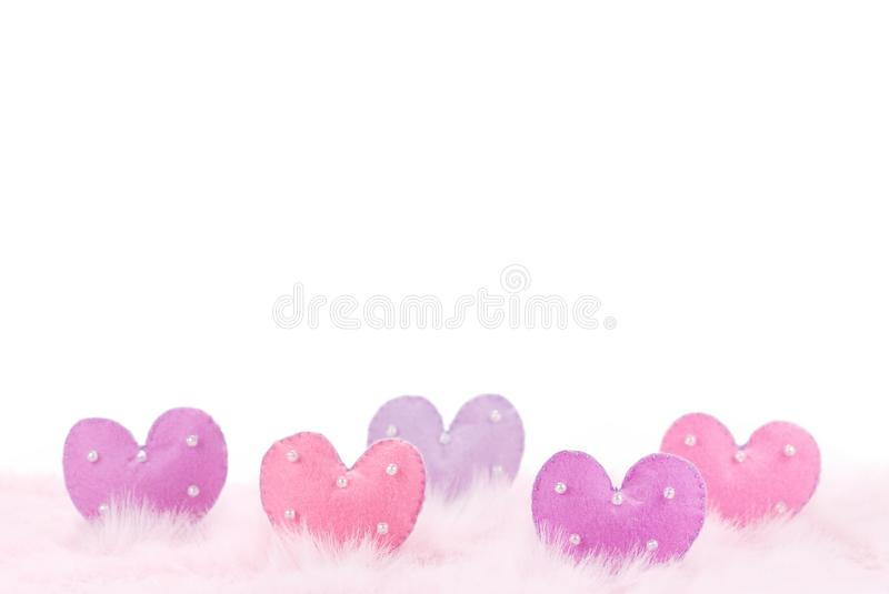 Colorful hearts with bead on pink feather. Colorfu hearts with bead on pink feather,large copy space stock photos