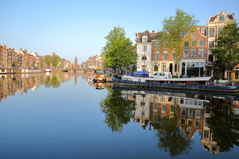 Colorful heritage buildings and houseboats, overlooking Zwanenburgwal canal and Amstel river with perfect reflections. With Munttoren historic tower with a royalty free stock images