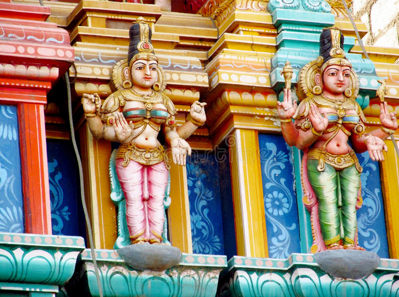 Colorful hindu statues on temple walls. Colored statue on the wall in front of the entrance to the hindu temple with ornament and decorations. Man and woman royalty free stock photos