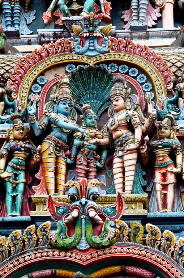 Colorful hindu statues on temple walls. Colored statue on the wall in front of the entrance to the hindu temple with ornament and decorations. Man and woman stock photo