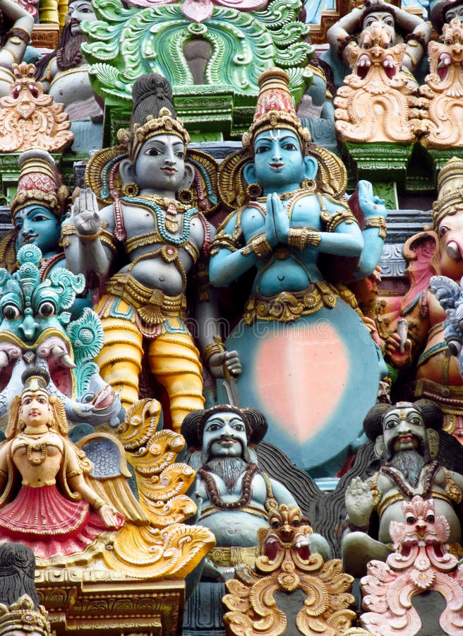 Colorful hindu statues on temple walls. Colored statue on the wall in front of the entrance to the hindu temple with ornament and decorations. Man and woman royalty free stock images