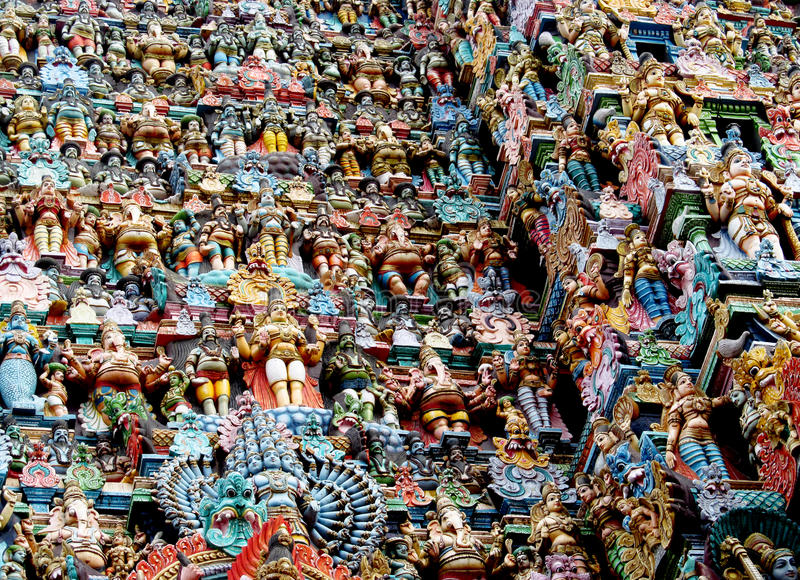 Colorful hindu statues on temple walls. Colored statue on the wall in front of the entrance to the hindu temple with ornament and decorations. Man and woman royalty free stock photo