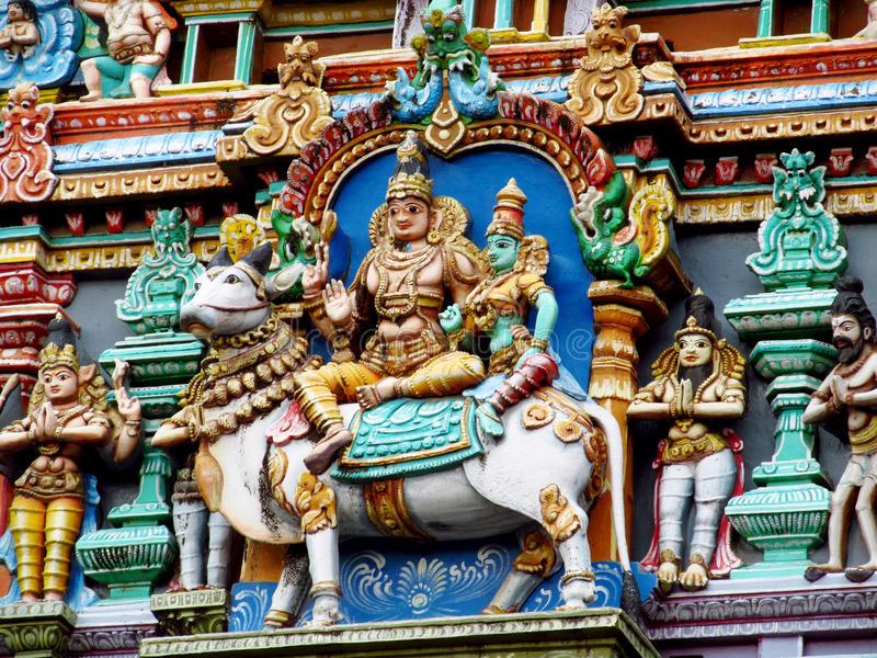 Colorful hindu statues on temple walls. Colored statue on the wall in front of the entrance to the hindu temple with ornament and decorations. Man and woman royalty free stock image