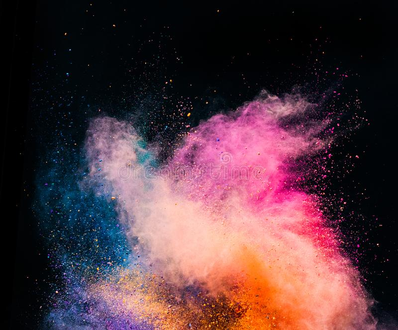 Colorful holi powder blowing up on black background. royalty free stock photography